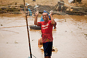 08 APRIL 2010 - NAKHON PHANOM, THAILAND: People fish in a pond in Non Siivilai, Nakhon Phanom province, Thailand. The pond is controlled by a nearby Buddhist temple which allows people to pay a small fee and fish in the pond one day per year. It's a fund raiser for the temple. This year the pond was less than half its normal size and the fishing catch was much smaller than normal. According to people who live here, the Mekong River is at its lowest point in nearly 50 years. Many of the people who live along the river farm and fish. They claim their crops yields are greatly reduced and that many days they return from fishing with empty nets. The river is so shallow now that fisherman who used to go out in boats now work from the banks and sandbars on foot or wade into the river. In addition to low river levels the Isan region of Thailand is also in the midst of a record drought and heat wave. Farmers have been encouraged to switch from rice to less water intensive crops and to expect lower yields. Farmers here rely more on rain fall than irrigation to water their crops.       PHOTO BY JACK KURTZ