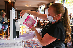 © Licensed to London News Pictures. 26/10/2020. London, UK. A staff member wearing a face covering pours in a sanitiser station in a Wetherspoons pub in north London. The hospitality industry estimates that pubs, bars and restaurants have spent £900million on screens, masks and hand sanitisers to make their venues safe for reopening, following the easing of COVID-19 lockdown restrictions. It has been reported that each pub has spent more than £10,000 adapting the interiors of their venues but with the latest restrictions, many now only serve customers outside their premises. Wetherspoons has spent £13.1million on getting its 875 pubs ready. Photo credit: Dinendra Haria/LNP