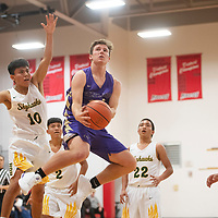 Kirtland Central's Brock Dowdy (24) drives to the basket against Newcomb in the Eddie Peña Classic Basketball Tournament Thursday in Grants.
