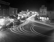 9345-54. St. Johns, Oregon.  Night view looking north on North Jersey (which is now N. Lombard) from the main intersection of N. Philadelphia showing St. Johns central business district. October 1926 (dated by sign on lower right).