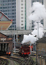© Licensed to London News Pictures. 13/01/2013, London, UK. Railway workers watch the newly restored Met Locomotive No. 1 steam engine prepare to leave a train depot in London, Sunday, Jan. 13, 2013. The engine will travel through part of the original underground route to mark the 150th anniversary of the opening of the world's first underground in January 1863, and linked to it will be the oldest surviving operational underground carriage, the Metropolitan Railway Jubilee Carriage 353, a set of four Chesham carriages and the world's oldest electric locomotives in service, No 12 Sarah Siddons. Photo credit : Sang Tan/LNP