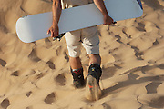 Sand boarder walking with his board in the Namib Desert, near Swakopmund, Namibia