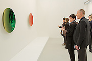 New York, NY - 6 May 2016. Frieze New York art fair. Visitors in the Lisson Gallery looking at Anish Kapoor's two concave mirror sculptures.
