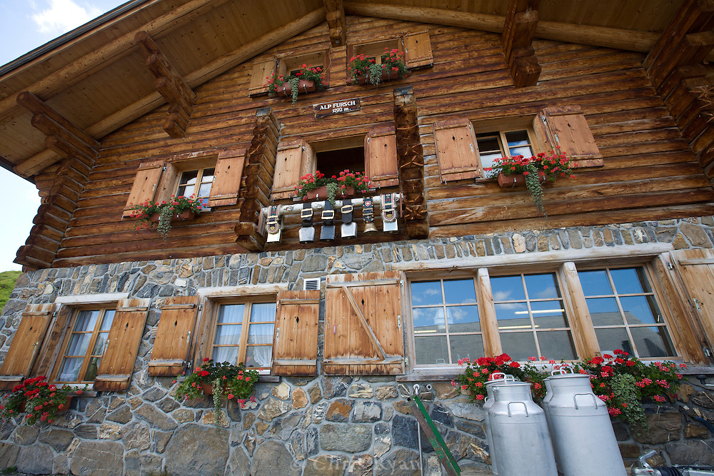 Cowbells and milk jugs in front of farmhouse in the Swiss Alps, Flumserberg, Sarganserland, Switzerland