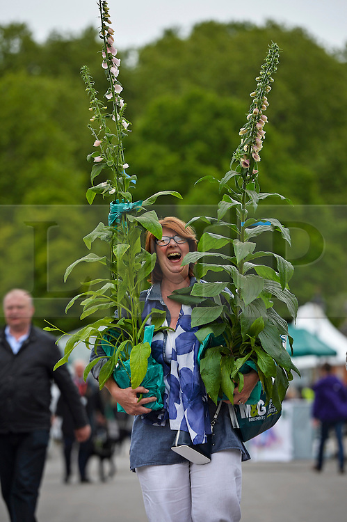 © London News Pictures. 23/05/2015. London, UK. Ellie Tinley with the flowers she bought. Members of the public carry exhibitors' plants from the 2015 Chelsea Flower show, which ends today (Sat). The Royal Horticultural Society flagship flower show has been held at the Royal Hospital in Chelsea since 1913. Photo credit: Ben Cawthra/LNP