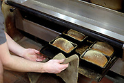 Freshly baked bread coming out of the oven at the Haxby Bakehouse, Yorks artisan bakery in Haxby, North Yorkshire, United Kingdom on 17th February 2017. Haxby Bakehouse make bread using traditional methods of slow fermentation. They use low yeasted overnight sponges, natural sourdough levain or a combination of the two. This means the bread they produce is full of flavour without the use of any artificial flour improvers, preservatives or emulsifiers.