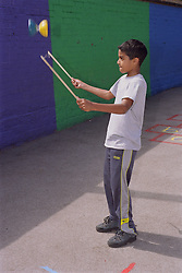 Young boy tossing diabolo in playground,