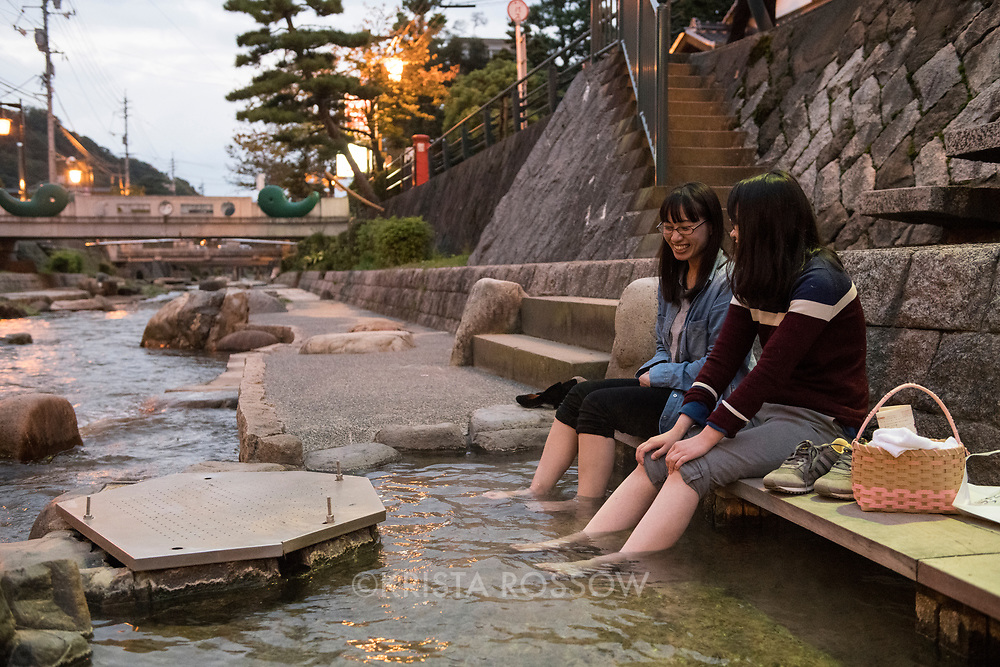 Two young Japanese women (model released) soak their feet in a public foot bath on the Tamayu River. Tamatsukuri Onsen is a hot spring village located near Matsue in the Shimane Prefecture of Japan. The hot spring's water is used in various bathing facilities and inns and in public foot baths located along the Tamayu River.