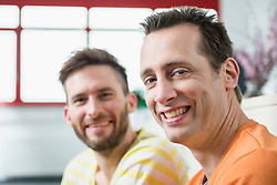 Two young men office portrait smiling meeting