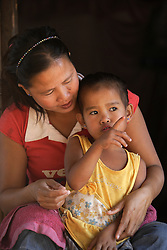 Lang and her mother Bounlid talk on the steps of their simple bamboo-walled home.<br /> Lang is 5 years old today, January 16th 2010.  Lang's mother Bounlid was photographed in the 6 months before giving birth and each year for the following 5 years following the birth, for the WHO Great Expectations project. <br /> Huey Kham Village, Santhong District, Vientiane Province, Lao PDR