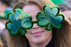 London, March 13th 2016. The annual St Patrick's Day Parade takes place in the Capital with various groups from the Irish community as well as contingents from other ethnicities taking part in a procession from Green Park to Trafalgar Square.  PICTURED: A woman in clover leaf glasses watches the procession. ©Paul Davey<br /> FOR LICENCING CONTACT: Paul Davey +44 (0) 7966 016 296 paul@pauldaveycreative.co.uk