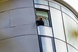 A man examines window attachments in the 27th storey penthouse apartment at The Corniche as a police cordon surrounding a forensics tent remains in place outside on the Albert Embankment in London after a window pane fell yesterday morning killing passing coach driver Mick Ferris. Albert Embankment, London, October 03 2018.
