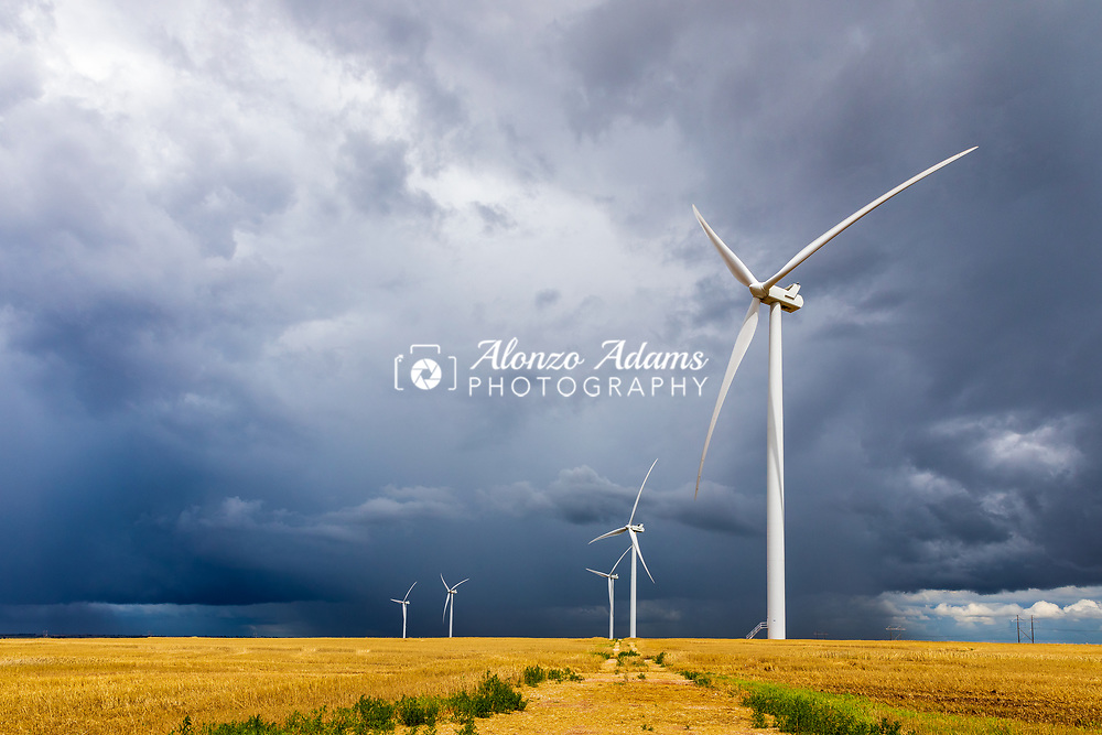 Wind Turbines in central Oklahoma with a thunderstorm in the background on Sunday, June 16, 2019. Photo copyright © 2019 Alonzo J. Adams.