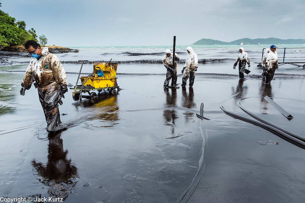 30 JULY 2013 - KOH SAMET, RAYONG, THAILAND:   Workers walk out of oily ocean water after laying out hoses to suck up oil on Ao Prao beach on Koh Samet island. About 50,000 liters of crude oil poured out of a pipeline in the Gulf of Thailand over the weekend authorities said. The oil made landfall on the white sand beaches of Ao Prao, on Koh Samet, a popular tourists destination in Rayong province about 2.5 hours southeast of Bangkok. Workers from PTT Global, owner of the pipeline, and up to 500 Thai military personnel are cleaning up the beaches. Tourists staying near the spill, which fouled Ao Prao beach, were evacuated to hotels on the east side of the island, which was not impacted by the spill. PTT Global Chemical Pcl is part of state-controlled PTT Pcl, Thailand's biggest energy firm.    PHOTO BY JACK KURTZ