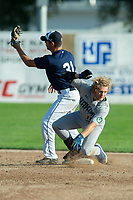 KELOWNA, BC - JULY 24:  Second baseman, Brett Tressen #31 of the Kelowna Falcons, catches the ball as Nick Israel #10 of the Yakima Valley Pippins slides in to second base at Elks Stadium on July 24, 2019 in Kelowna, Canada. (Photo by Marissa Baecker/Shoot the Breeze)