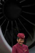 Cabin crew hostess and engine turbofan blades of a Qatar Airways Boeing 787 at the Farnborough Air Show, UK.