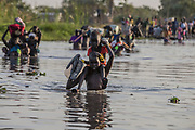 Internally displaced civilians arrive at a shore after crossing a swamp to reach a registration area prior to a food distribution carried out by the United Nations World Food Programme (WFP) in Thonyor, Leer County, South Sudan, February 25, 2017.