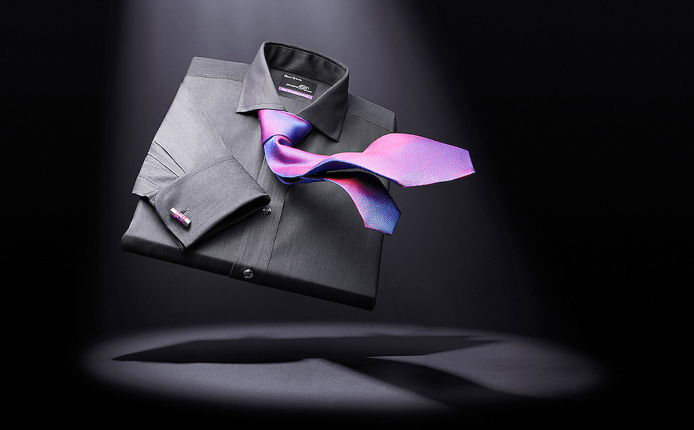 Black shirt with purple tie in a spot light.