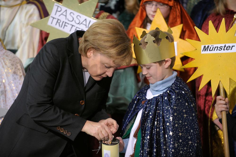 04 JUN 2008, BERLIN/GERMANY:<br /> Angela Merkel, CDU, Bundeskanzlerin, steckt ihre Spende in die Spendendose von einem der Heiligen drei Koenige, waehrend dem Empfang der Sternsinger im Bundeskanzleramt<br /> IMAGE: 20080104-01-024<br /> KEYWORDS: Heilige drei Koenige, Heilige drei Könige, spendet, Geld, Geldscheine, Kanzleramt