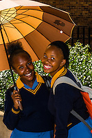 School girls carry an umbrella to shield themselves from the sun, Mkize Street, Rockville, Soweto, Johannesburg, South Africa.