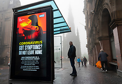 Edinburgh, Scotland, UK. 13 June 2020. On a foggy wet Saturday afternoon the streets of Edinburgh city centre remain very quiet and shops and businesses remain closed. Lockdown is expected to be relaxed next month. Video display screen at bus stop displays Coronavirus health warning messages.   Iain Masterton/Alamy Live News