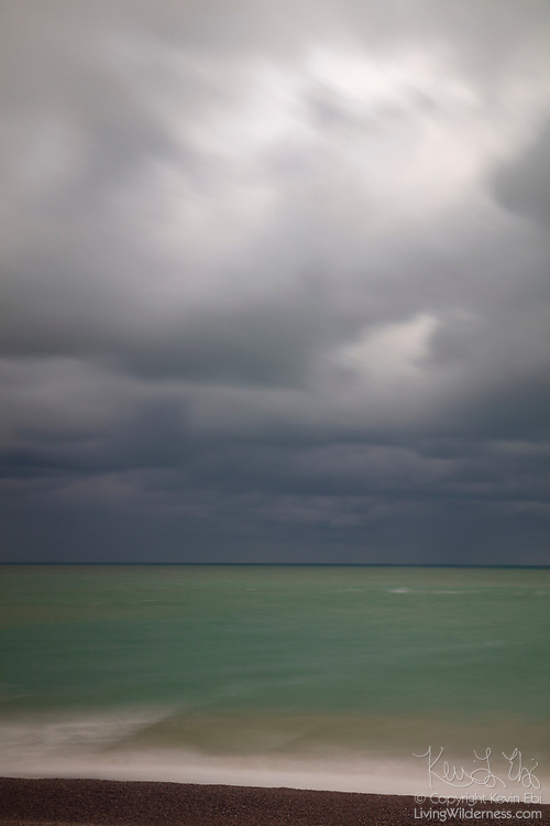 Dark storm clouds pass over the green water of the English Channel as viewed from the beach at Fécamp in the Normandy region of France.