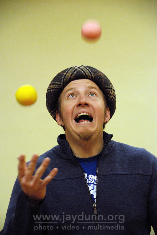 """USA, Chicago, IL, December 12, 2009. Instructor Paul Lopez demonstrates presentation while juggling. Students in the """"At-Risk After School Program"""" at Maria Saucedo Scholastic Academy receive training in basic physics principles through an innovative new program called """"Circus Galactica"""" put on by Pros Arts, a non-profit organization founded in 1978 by professional artists dedicated to the Pilsen/Little Village communities. In a residency that directly integrates science and art, veteran circus performers Douglas Grew and Paul Lopez bring the importance of """"balance, focus and presentation"""" into hands-on lessons about gravity, inertia, and the dynamics of objects in motion. Photo for Hoy by Jay Dunn."""
