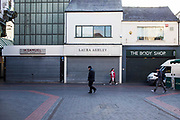 A row of famous British high street shops, The Body Shop, Laura Ashley and H Samuel in Middlesborough town centre, North Yorkshire, United Kingdom.  All the shops are closed with the window shutters down.