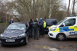 Harefield, UK. 14 January, 2020. Enforcement agents working on behalf of HS2 liaise with a police officer during the attempted eviction of a Stop HS2 protection camp. Part of the nearby Colne Valley protection camp was evicted by bailiffs last week. 108 ancient woodlands are set to be destroyed by the high-speed rail link and further destruction of trees for HS2 in the Harvil Road area is believed to be imminent.