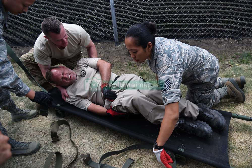 Tech. Sgt. Frank Yuvan, left, an Independent Duty Medical Technician from the 421st Combat Training Squadron, and Tech. Sgt. Deborah Macalalad, an aerospace medical technician from the 108th Medical Group, put Pete Brierton, Disaster Medical Assistance Team medic, onto a litter during Patriot North 18 at Volk Field, Wis., July 18, 2018. Patriot is a domestic operations disaster-response training exercise conducted by National Guard units working with federal, state and local emergency management agencies and first responders. (U.S. Air National Guard photo by Senior Airman Julia Santiago)