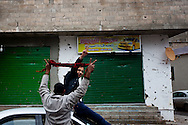 Protesters drive by bullet holes from mercenary forces in Banghazi on Feb. 25, 2011.