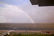 Rainbow at Afsluitdijk, a dam separating the North Sea from the Ijsselmeer lake. View from bridge at Breezanddijk, an artificial island created by building the  dam across the entrance to the ZuiderZee