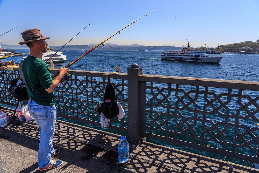 Istavrit (a.k.a. horse mackerel) fisherman and on Galata Bridge in Istanbul, Turkey.