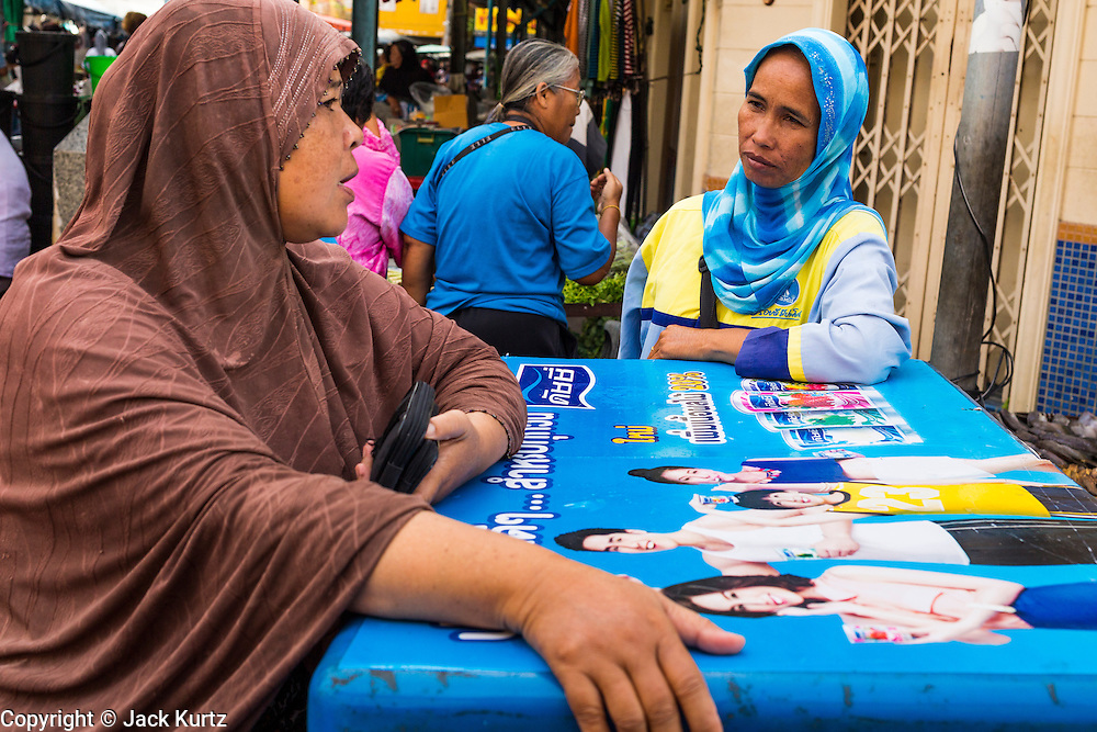 09 JULY 2013 - PATTANI, PATTANI, THAILAND:  Women chat over a cooler chest of a yogurt drink in the market in Pattani.  Pattani, along with Narathiwat and Yala, are the only three Muslim majority provinces in Thailand.     PHOTO BY JACK KURTZ