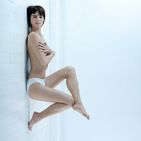 young beautiful woman lying on floor topless underwear hands hiding breast