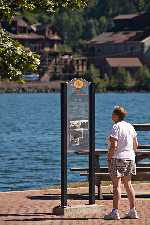 A person reads a historical marker along the waterfront of the Portage Canal between the cities of Houghton and Hancock Michigan.
