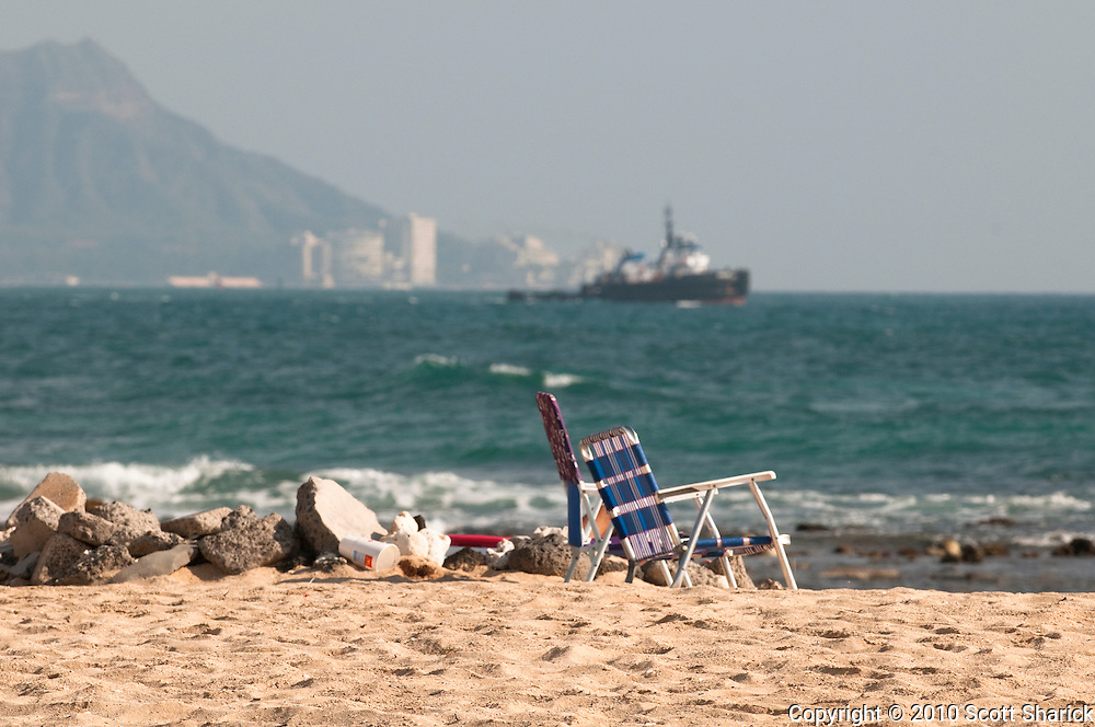 Empty beach chairs sit in the sand on Sand Island as a ship passes in the distance in front of Diamond Head.