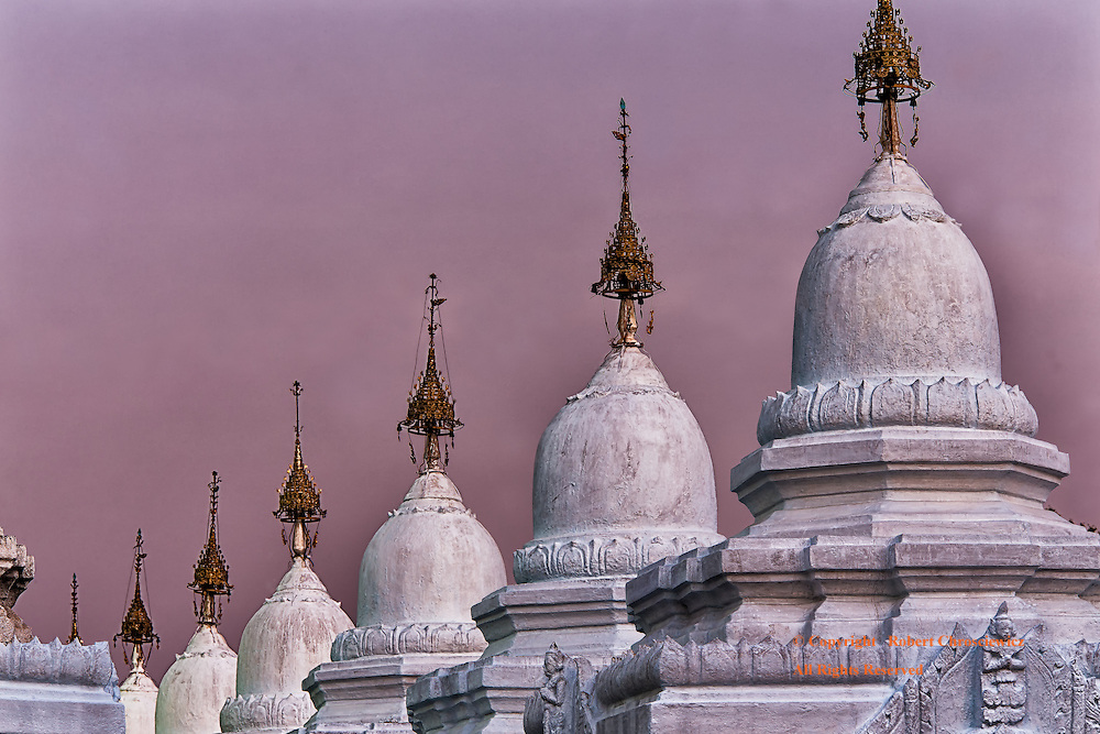 Mauve Evening: The tail end of a firery sunset provides a mauve cast; set upon both the sky and the Buddhist Kyauksa Gu (stone-inscription caves) at the Kuthodaw Pagoda, Mandalay Myanmar.