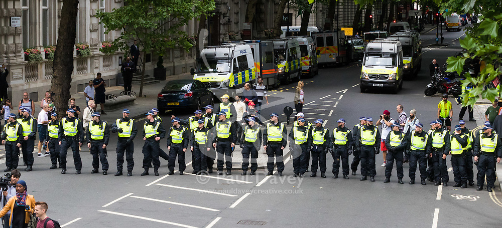 London, June 24th 2017. Anti-fascist protesters counter demonstrate against a march to Parliament by the far right anti-Islamist English Defence League. PICTURED: Police form a barrier across Nothumberland Avenue.