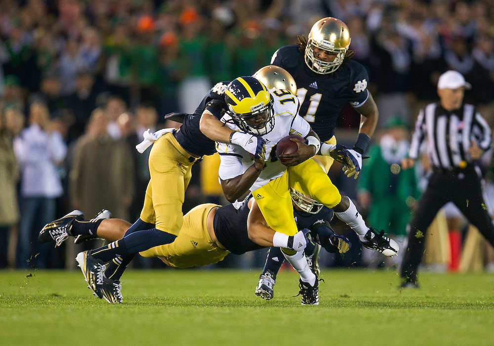 September 22, 2012:  Michigan quarterback Denard Robinson (16) is tackled by Notre Dame players during NCAA Football game action between the Notre Dame Fighting Irish and the Michigan Wolverines at Notre Dame Stadium in South Bend, Indiana.  Notre Dame defeated Michigan 13-6.