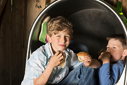 Two boys eating muffins in playground, Munich, Bavaria, Germany