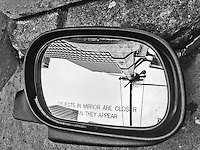 Passenger-side automobile mirror laying on the street, facing up at the curb, showing the reflection of a skyscraper