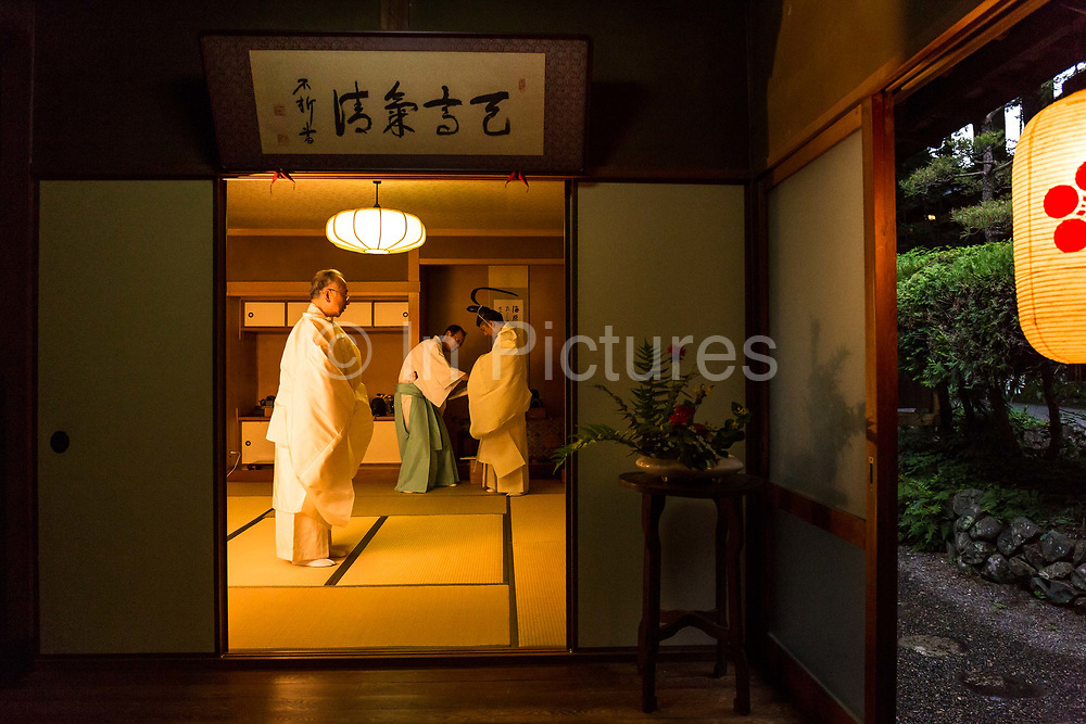 Shinto priest Masatsugu Okutani, 41 dresses into his ceremonial clothes in preparation for the Summer Grand Purification ceremony to be held at the Yabuhara Sanctuary, with his father Kazufumi Okutani, 71. They are the  24th and 25th uninterrupted generational SHINTO priests in their family line dating back to the 12th century AD. The essence of the ceremony is to remove temporarily all impurities such as rational thought from ones body and mind and maximize ones sensitivities. In other words to be in a state of heightened concentration of the here and now and allow ones sensitivities to be replenished as they are a constant source of japanese cultural identity, Kiso Mura village.