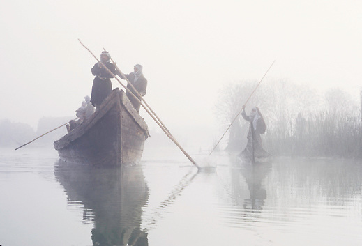Marsh Arabs pole boat on misty morning in the marshes of Southern Iraq, Middle East