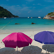 Colorful beach umbrellas on idyllic beach of Raya island, Thailand