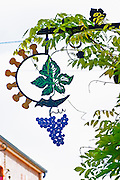A wrought iron painted sign that illustrates the theme of champagne and wine production: a vine leaf champagne corks and a bunch of grapes, the village of Hautvillers in Vallee de la Marne, Champagne, Marne, Ardennes, France