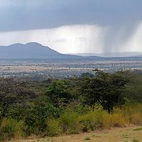 Africa, Kenya, Masai Mara. Rains sweep across the plains of the Maasai Mara and Serengeti border region.