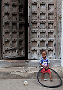 A young boy is photographed with a deflated bicycle tire in Stone Town in Zanzibar, Tanzania.