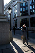 Scene in the City of London in the afternoon winter light. An office worker walks past an old fashioned street lamp with her lunch in a paper bag.
