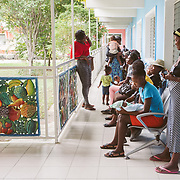 INDIVIDUAL(S) PHOTOGRAPHED: N/A. LOCATION: St. Damien Hospital, Nos Petits Frères et Sœurs, Tabarre 41 Commune, Haïti. CAPTION: People waiting for treatment at St. Damien's Hospital. A young mother, Maricia Agenur, is waiting with her little baby at the front of the line.